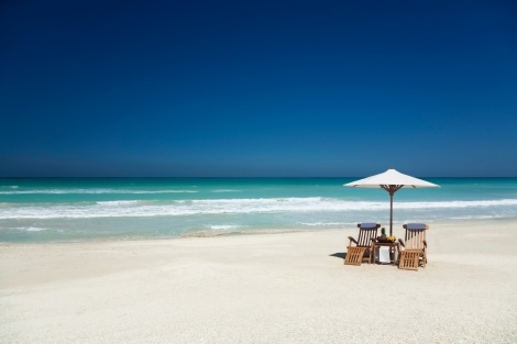 two teak chairs with white umbrella on a beach
